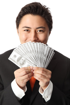 Attractive businessman wearing a suit and tie, holding a fan of hundred dollar bills in front of his face  photo
