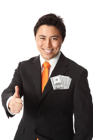 Attractive businessman wearing a suit and tie, with hundred dollar bills in his pocket  photo