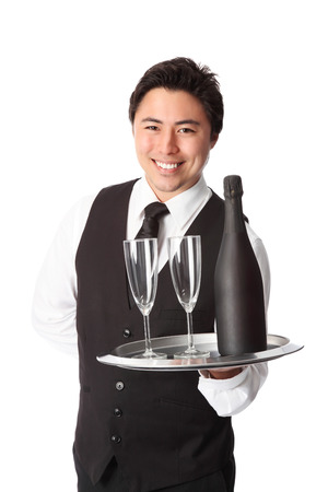 Attractive waiter with bottle and glasses, wearing a black vest  photo