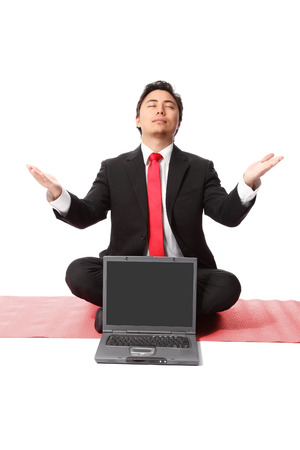Businessman sitting on the floor with a laptop computer in front of him  White background