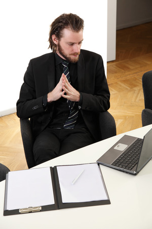 Attractive businessman in a suit and tie, sitting in a board room with a laptop and clipboard in front of him  photo