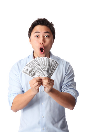 Attractive man wearing a shirt, holding a fan of dollar bills in front of him  White background