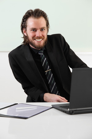 Attractive businessman working on a computer sitting an a board room with a whiteboard behind him  photo