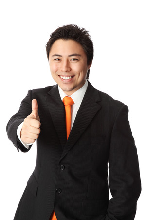 well made: Attractive businessman in a suit and tie, doing thumbs up  White background