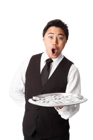 Attractive waiter in a vest and shirt, holding a tray with dollar bills  White background  photo