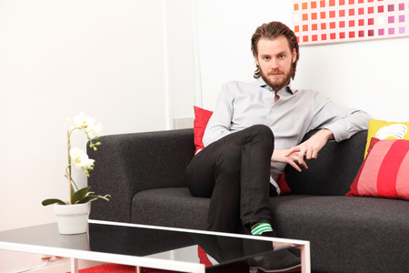 Attractive man wearing a shirt and jeans, sitting down in a sofa  Stock Photo