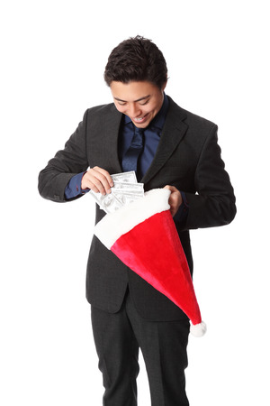 christmas bonus: Attractive businessman standing wearing a suit and tie, holding a christmas hat full of money  Christmas bonus  White background