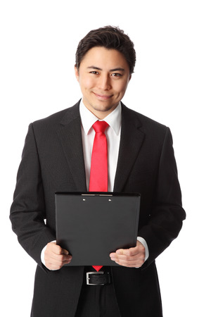 Young attractive businessman wearing a black suit and red tie. Holding a clipboard. White background.