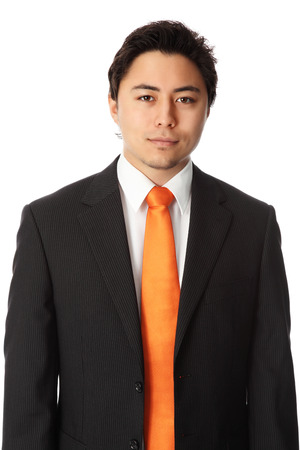 Young attractive businessman wearing a suit and orange tie. White background. photo