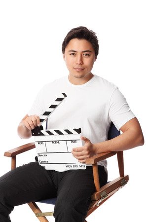 Young attractive man holding a film slate, wearing a white t-shirt. White background. photo