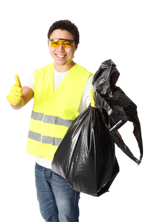 Young standing wearing a reflective vest, gloves and safety glasses. Holding a black garbage bag. White background. photo