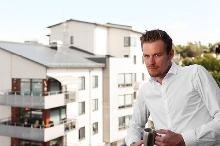 Attractive young man standing on a balcony holding a coffee mug, Wearing a white shirt. photo