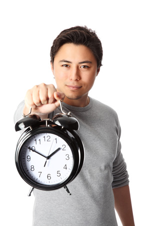 Young attractive man holding a clock. Wearing a grey shirt. White background. photo