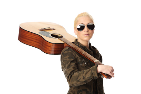 Attractive blonde woman standing wearing a military jacket with big sunglasses, holding a guitar. White background. photo