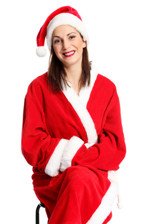 mrs  santa claus: A young cute and attractive Mrs Santa Claus sitting down on a chair, wearing a red costume and hat. White background. Stock Photo