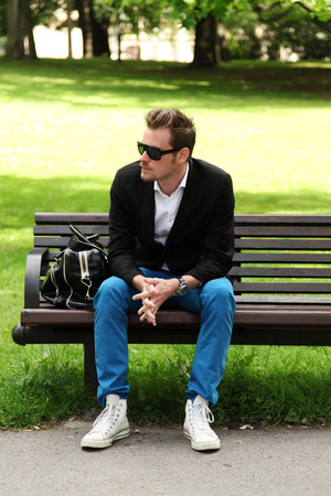 Man sitting down on a bench in a park wearing jeans and blazer on a sunny summer day.