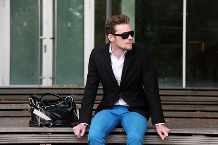 man with glasses: A man sitting outside wearing black sunglasses and a black jacket with blue jeans.