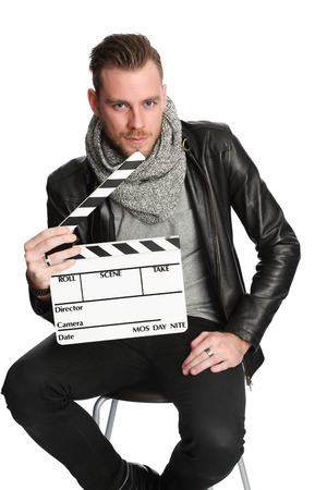 Attractive young man in his 20s sitting down wearing a black leather jacket holding a film slate. White background.