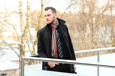 Young businessman wearing a shirt and tie with a jacket and scarf, standing outside on a cold winters day.