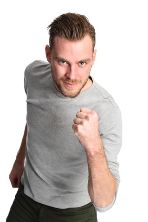 rolled up sleeves: Attractive man wearing a grey shirt standing against a white background with raised fist.