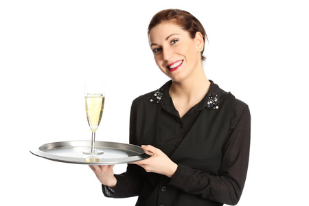 A cute brunette waiter serving two glasses of champagne on a serving tray, wearing a black shirt with a black vest. White background.