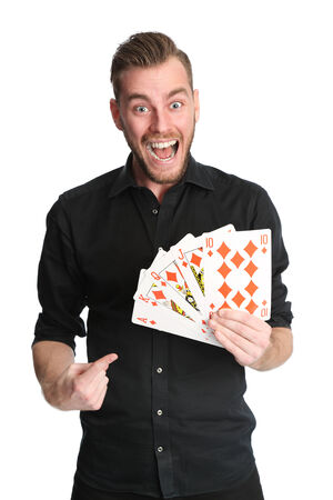 rolled up sleeves: Young and attractive man wearing a black shirt with his sleeves rolled up, holding a fan of a royal flush in diamonds on big sized cards. Stock Photo