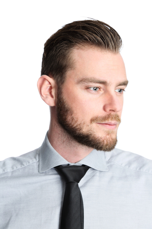 An attractive businessman wearing a grey shirt with a black tie, standing focused against a white background. Studio shot.