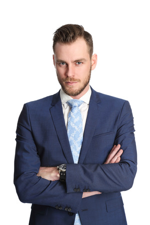 An attractive businessman wearing a blue suit and tie, standing in a studio with white background. photo