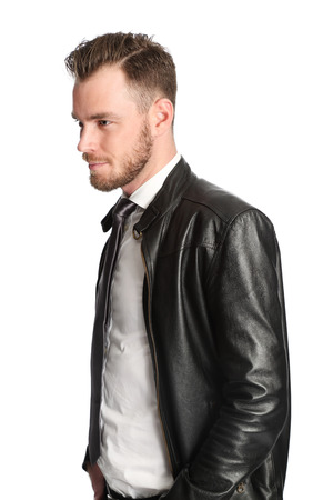 Attractive man wearing a white shirt, black tie and a black leather jacket. White background.