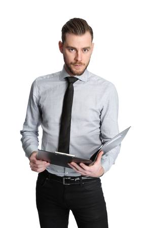An intense businessman wearing a grey shirt and black tie, holding a clipboard in a studio setting. White background. photo