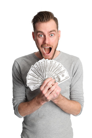 Attractive man wearing a shirt, holding a fan of dollar bills in front of him. White background. photo