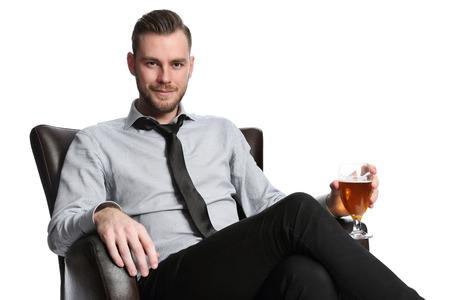 after to work: Un hombre de negocios joven y atractiva sentado despu�s del trabajo con una cerveza bien fr�a, se relaja en un sof� vestido con una camisa y corbata. Fondo blanco. Foto de archivo