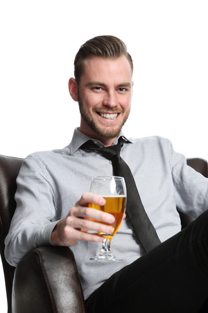 beer after work: A young and attractive businessman sitting down after work with a cold beer, relaxing in a couch wearing a shirt and tie. White background.