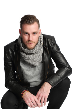 A trendy and modern attractive man standing in a studio setting wearing a black leather jacket, grey shirt and a grey scarf. White background.