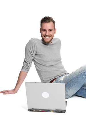 laying down: A young and attractive man wearing a grey shirt and jeans, laying down on the floor with a laptop computer in front of him. White background.