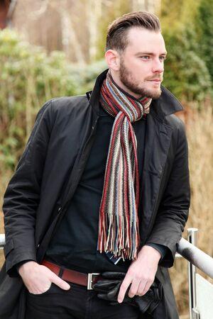 in jeans: Hombre de negocios joven que llevaba una camisa y una corbata con una chaqueta y una bufanda, de pie fuera en un d�a fr�o.
