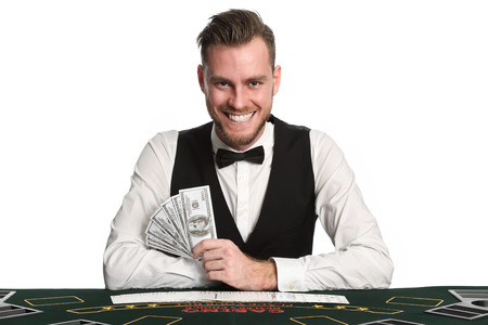Mature casino worker wearing a black vest and white shirt with a bowtie. Holding a fan of dollar bills with a deck of cards spread in front of him. White background. photo