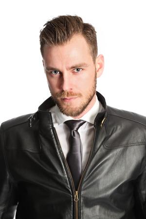 Aantrekkelijke man draagt een wit shirt zwarte das en een zwarte leren jas. Witte achtergrond. Stockfoto