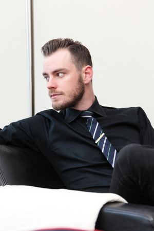 arm chair: A relaxed businessman sitting down in an arm chair, in a lounge room wearing a shirt and tie.