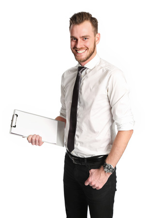 An attractive businessman wearing a wihte shirt and grey tie standing against a white background holding a clipboard.