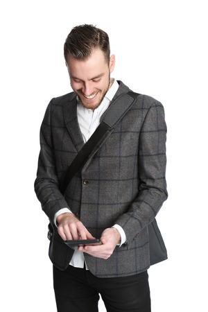 relajado: Apuesto hombre de unos 20 a�os que llevaba una chaqueta gris con una camisa blanca con un bolso de la computadora que cuelga en su hombro. La celebraci�n de una tableta digital. Fondo blanco.