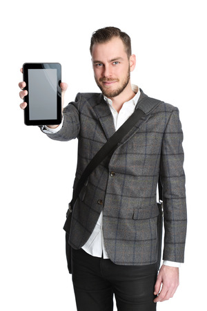 Handsome man in his 20s wearing grey jacket with a white shirt with a computer bag hanging on his shoulder. Holding a digital tablet. White background.