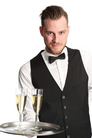 champagne glass: Young attractive waiter wearing a white shirt and black vest serving 2 glasses of champagne. White background. Stock Photo