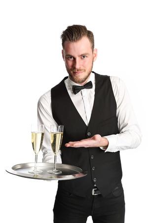 trays: Camarero atractiva joven con una camisa blanca y un chaleco negro que sirve 2 copas de champ�n. Fondo blanco. Foto de archivo