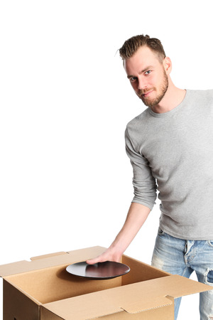 Man wearing a grey shirt holding a black plate with a big cardboard box standing beside him. Shot in a studio with a white background.