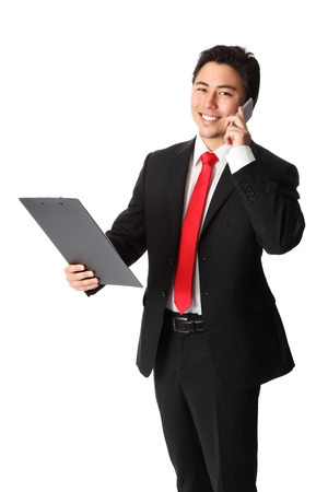 Young attractive businessman working on the phone wearing a suit and tie and holding a clipboard. White background.