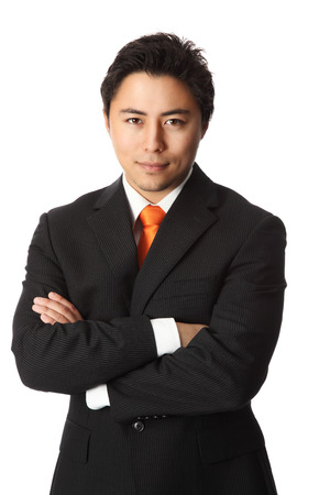 20s: Attractive businessman in his 20s wearing a black striped suit with an orange tie. White background.
