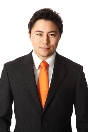 well made: Attractive businessman in his 20s wearing a black striped suit with an orange tie. White background.