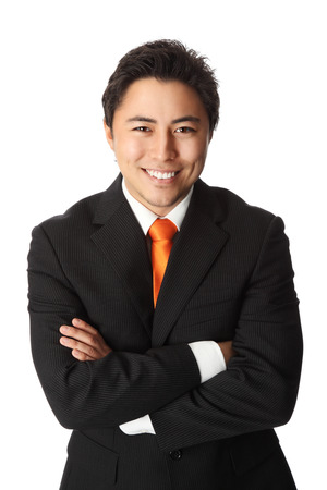 Attractive businessman in his 20s wearing a black striped suit with an orange tie. White background.