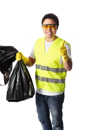 garbage bag: Young man standing wearing a reflective vest gloves and safety glasses. Holding a black garbage bag doing thumbs up. White background. Stock Photo